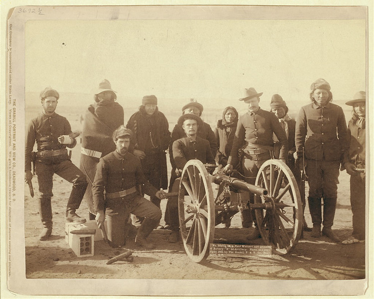 "Description of  Seven Lakota scouts and four uniformed Euro-Americans posed behind an artillery piece or Hotchkiss gun, probably in the Pine Ridge Reservation near Wounded Knee, South Dakota. ""Copr. Paul Wernert [i.e. Weinert] and gunners of Battery ""E"" 1st Artillery / photo. and copyright 1891 by the Grabill P. & V., Deadwood, S.D."" (Library of Congress Prints and Photographs Division)"