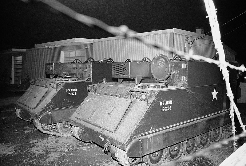 Description of  Two armored personnel carriers wait in the darkness near Bureau of Indian Affairs headquarters on Feb. 28, 1973 in Wounded Knee. Federal marshals spent part of the day Wednesday where a group Indians have hostages (AP Photo)