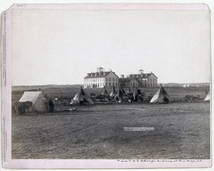 Description of  Title: U.S. School for Indians at Pine Ridge, S.D.<br />Small Oglala tipi camp in front of large government school buildings in open field. 1891.<br />Repository: Library of Congress Prints and Photographs Division Washington, D.C. 20540