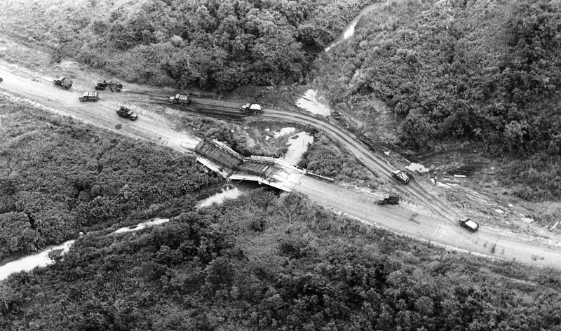 Description of  South Vietnamese supply trucks take a detour around a destroyed bridge en route to Pleiku on Route 19, July 18, 1965. The original bridge, and a temporary bridge placed on top of it, were both destroyed by the Viet Cong. (AP Photo/Eddie Adams)