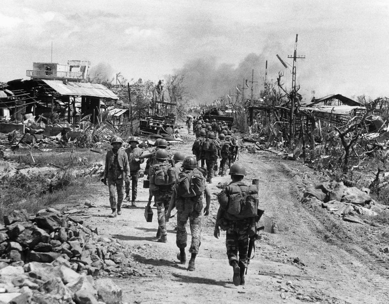 Description of  A line of South Vietnamese troops move along a devastated street in Quang Tri City as the battle continues for the provincial capital on July 28, 1972. Government forces were the midst of a campaign to retake the northern South Vietnamese city which was captured by enemy forces two months earlier. (AP Photo)