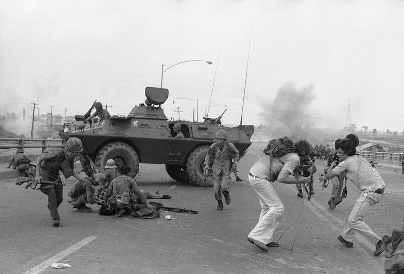 Description of  South Vietnamese troopers and western TV newsmen run for cover as North Vietnamese mortar round explodes on Newport Bridge in the outskirts of Saigon on Monday, April 28, 1975. (AP Photo/Hoanh)