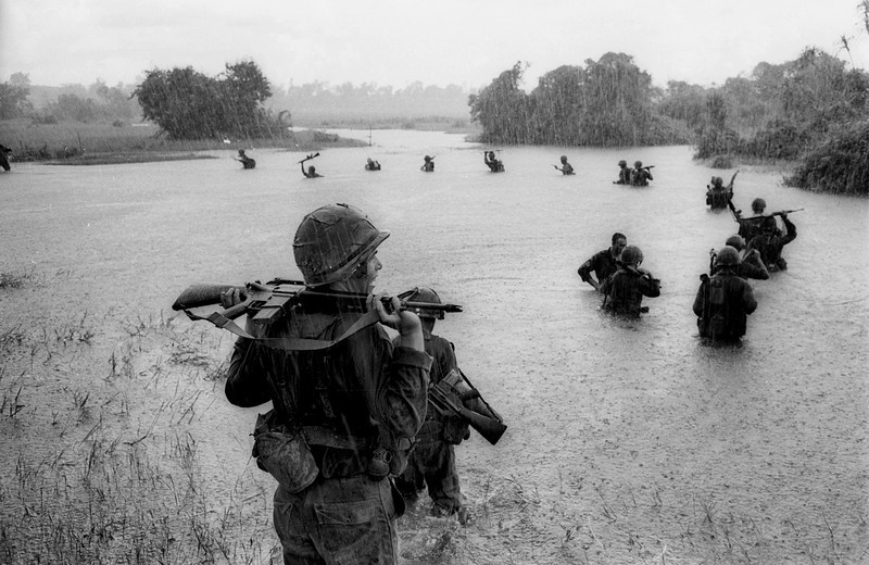 Description of  Paratroopers of the U.S. 2nd Battalion, 173rd Airborne Brigade hold their automatic weapons above water as they cross a river in the rain during a search for Viet Cong positions in the jungle area of Ben Cat, South Vietnam, Sept. 25,1965. The paratroopers had been searching the area for 12 days with no enemy contact. (AP Photo/Henri Huet)