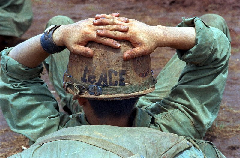 "Description of  With a helmet declaring ""Peace,"" a soldier of the 1st Cavarly Division, 12th Cavalry, 2nd Battalion, relaxes June 24, 1970, before pulling out of Fire Support Base Speer, six miles inside the Cambodian border.  The troops were returning to South Vietnam after operations against enemy sanctuaries in Cambodia.  (AP Photo)"