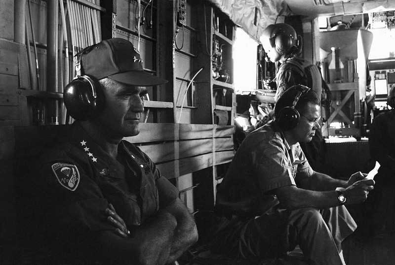 Description of  Defense Secretary McNamara and Gen. William Westmoreland, commander U.S. Forces in Vietnam, sit with muffler type radio earphones as they ride in helicopter toward the DMZ on McNamara's first field trip during his current visit to Vietnam, July 10, 1967. (AP Photo)
