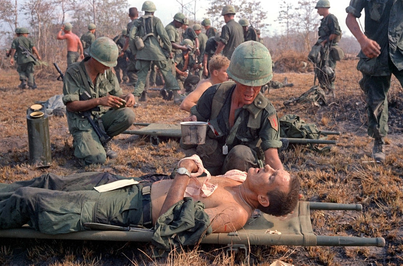 Description of  A wounded U.S. soldier of the 1st Infantry Division, 26th Infantry Regiment, 1st Battalion, receives first aid after being rescued from a jungle battlefield south of the Cambodian border in Vietnam's war zone C, April 2, 1967. A reconnaissance platoon ran into enemy bunkers, and their recuers were pinned down for four hours in fighting that left 7 U.S. dead and 42 wounded. (AP Photo)