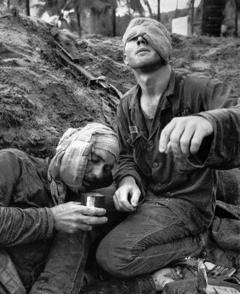 Description of  First Cavalry Division Medic Thomas Cole, from Richmond, Va., looks up with his one uncovered eye as he continues to treat a wounded Staff Sgt. Harrison Pell during a January 1966 firefight in the Central Highlands between U.S. troops and a combined North Vietnamese and Vietcong force. (AP Photo/Henri Huet)