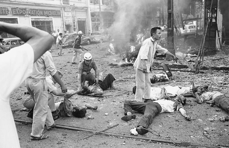 Description of  Injured Vietnamese receive aid as they lie on the street after a bomb explosion outside the U.S. Embassy in Saigon, Vietnam, March 30, 1965. Smoke rises from wreckage in the background. At least two Americans and several Vietnamese were killed in the bombing. (AP Photo/Horst Faas)