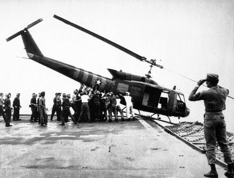 Description of  U.S. Navy personnel aboard the USS Blue Ridge push a helicopter into the sea off the coast of Vietnam in order to make room for more evacuation flights from Saigon, Tuesday, April 29, 1975.  The helicopter had carried Vietnamese fleeing Saigon as North Vietnamese forces closed in on the capital.  (AP Photo/jt)
