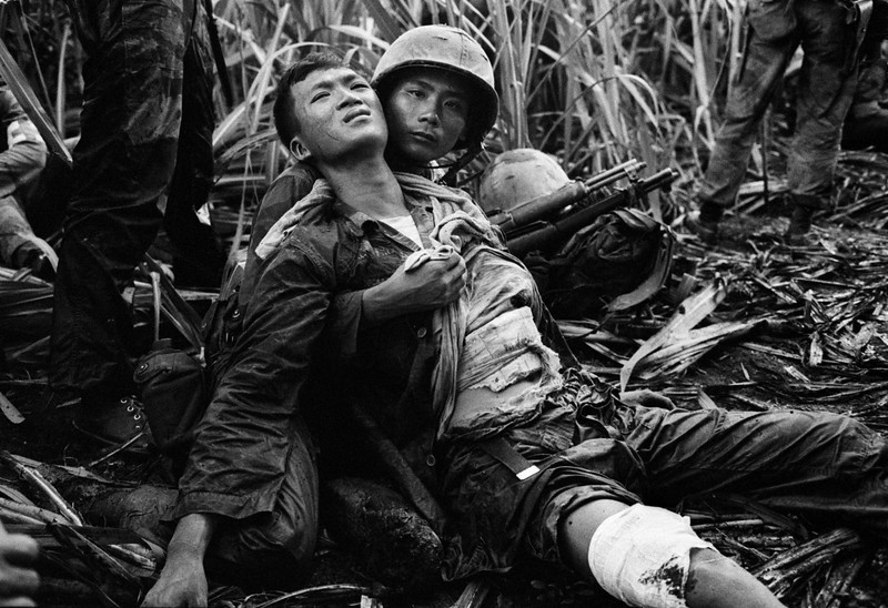 Description of  A South Vietnamese Marine, severely wounded in a Viet Cong ambush, is comforted by a comrade in a sugar cane field at Duc Hoa, about 12 miles from Saigon, Aug. 5, 1963. A platoon of 30 Vietnamese Marines was searching for communist guerrillas when a long burst of automatic fire killed one Marine and wounded four others. (AP Photo/Horst Faas)