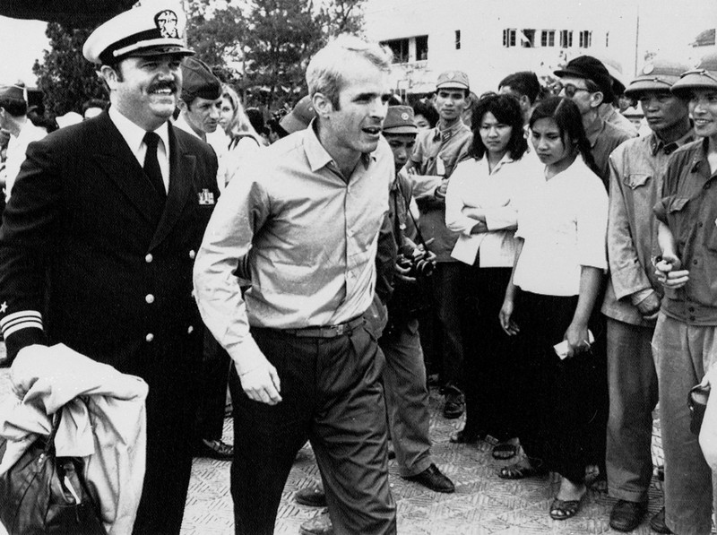 Description of  John S. McCain III is escorted by Lt. Cmdr. Jay Coupe Jr., public relations officer, March 14, 1973, to Hanoi's Gia Lam Airport after the POW was released.  (AP Photo/Horst Faas)