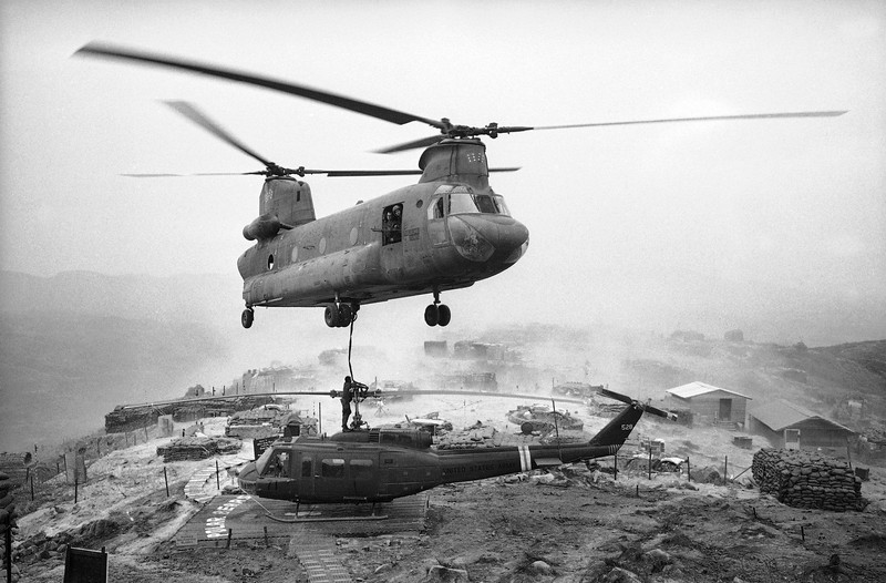 "Description of  At a hilltop firebase west of Chu Lai in Vietnam, a huge army ""Chinook"" helicopter prepares to lift a conked-out smaller one to a base for repairs, April 27, 1969. The firebase was named LZ West and was manned by the troopers of the 196th Light Infantry Brigade forming part of the American Division. The smaller helicopter - a Huey UH-ID - had developed engine trouble so its crew chief called in the local aerial towing service. One sturdy nylon strap to the chopper's winch and the two were off. (AP Photo/Oliver Noonan)"