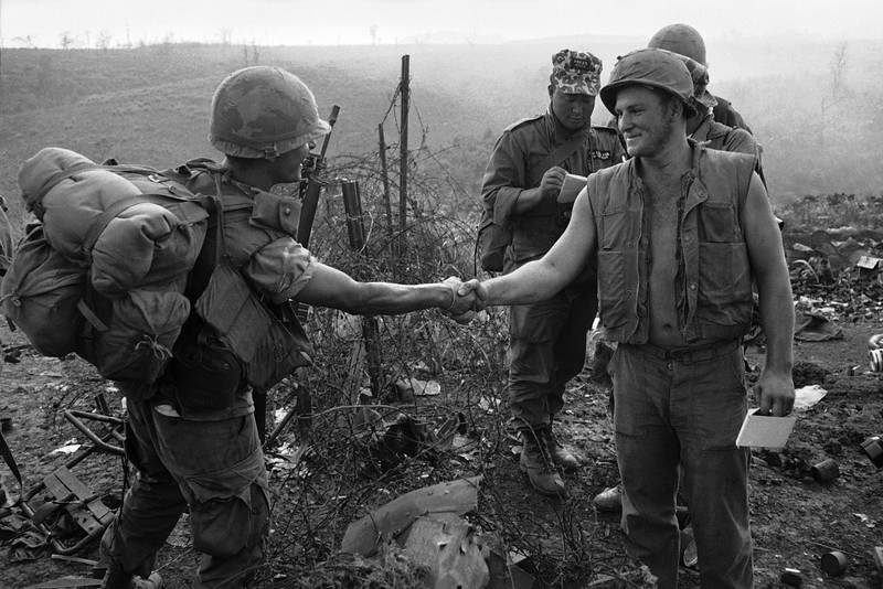 Description of  Pfc. Juan Fordona of Puerto Rico, a First Cavalry Division trooper, shakes hands with U.S. Marine Cpl. James Hellebuick over barbed wire at the perimeter of the Marine base at Khe Sanh, South Vietnam, early April 1968.  The meeting marked the first overland link-up between troops of the 1st Cavalry and the encircled Marine garrison at Khe Sanh.  (AP Photo/Holloway)