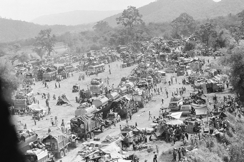 Description of  Hundreds of vehicles of all sorts fill an empty area as the refugees fleeing in the vehicles pause near Tuy Hoa in the central coastal region of South Vietnam, Saturday, March 23, 1975 following the evacuation of Banmethuout and other population centers in the highlands to the west. (AP Photo/Ut)