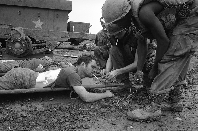 Description of  A medic lights a cigarette for Spec/5 Gary Davies of Scranton, Pa., awaiting evacuation by helicopter from Ben Het in South Vietnam where he was wounded, June 27, 1969. (AP Photo/Oliver Noonan)