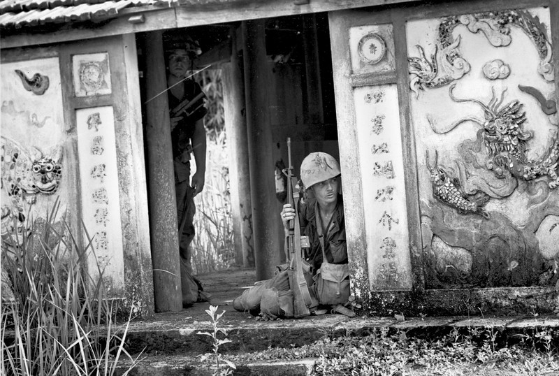 Description of  U.S. Marines of the 3rd Battallion, 4th Marines, crouch in the cover of a pagoda entrance as their patrol moves through a village along the Ben Hai river in the southern sector of the DMZ in South Vietnam, on May 22, 1967. The pagoda walls are richly decorated with images of dragons and snakes.  (AP Photo/Kim Ki Sam)