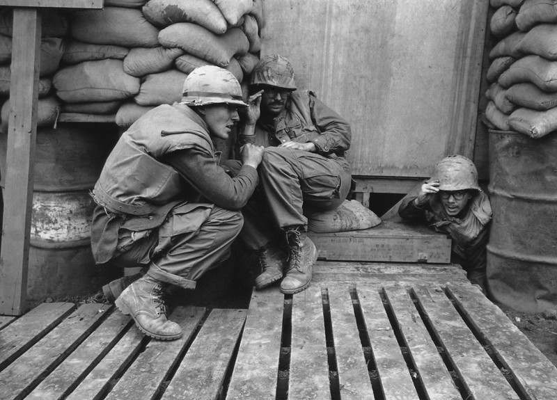 Description of  American soldiers take shelter in a sandbagged bunker as North Vietnamese rockets hit the U.S. Marine base at Khe Sanh on Feb. 24, 1968. (AP Photo/Rick Merron)