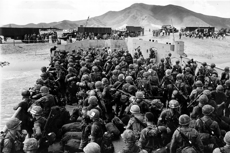 Description of  Elements of the U.S. First Cavalry Air Mobile division in a landing craft approach the beach at Qui Nhon, 260 miles northeast of Saigon, Vietnam, in Sept. 1965.  Advance units of 20,000 new troops are being launched for a strike on the Viet Cong during the Vietnam War.  (AP Photo)