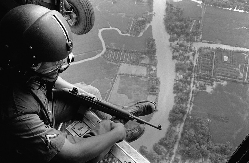 Description of  3A Helmeted U.S. Helicopter Crewchief, holding carbine, watches ground movements of Vietnamese troops from above during a strike against Viet Cong Guerrillas in the Mekong Delta Area, January 2, 1963. The communist Viet Cong claimed victory in the continuing struggle in Vietnam after they shot down five U.S. helicopters. An American officer was killed and three other American servicemen were injured in the action. (AP Photo)