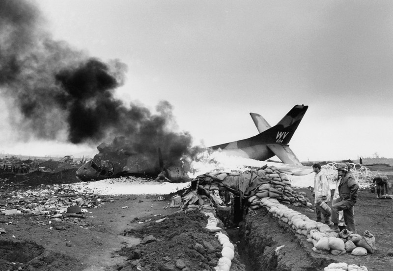 Description of  An American C-123 cargo plane burns after being hit by communist mortars while taxiing on the Marine post at Khe Sanh, South Vietnam on March 1, 1968. (AP Photo/Peter Arnett)