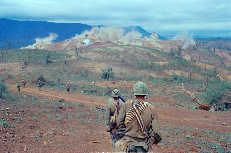 Description of  Air Cavalry troops taking part in Operation Pegasus are shown walking around and watching bombing on a far hill line on April 14, 1968 at Special Forces Camp at Lang Vei in Vietnam. (AP Photo/Richard Merron)