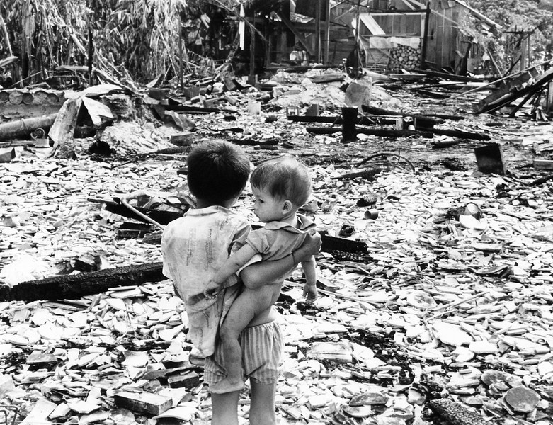 Description of  A small boy holds his younger brother and looks at the remains of what was once his village, Tha Son, South Vietnam, 45 miles Northwest of Saigon, Vietnam on June 15, 1969. He and his family fled the village when Viet Cong troops infiltrated. Counter-attacking allied troops used artillery and bombs to push the Viet Cong out. The allies had told the people to leave their homes before the barrage began. (AP Photo/Oliver Noonan)