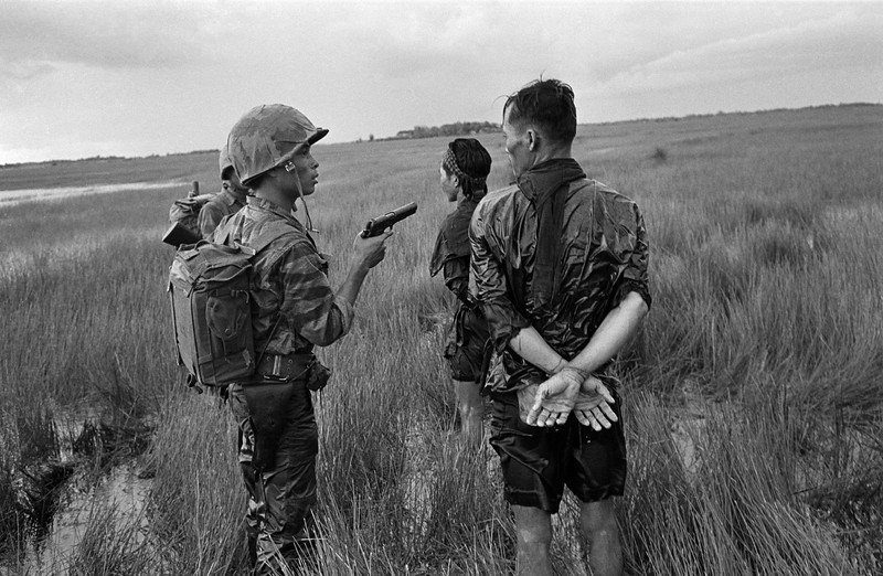 Description of  A South Vietnamese soldier holds a cocked pistol as he questions two suspected Viet Cong guerrillas captured in a weed-filled marsh in the southern delta region late in August 1962. The prisoners were searched, bound and questioned before being marched off to join other detainees. (AP Photo/Horst Faas)