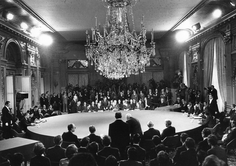 Description of  The four delegations sit at the table during the first signing ceremony of the agreement to end the Vietnam War at the Hotel Majestic in Paris, Jan. 27, 1973. Clockwise, from foreground, delegations of the Unites States, the Provisonal Revolutionary Government of South Vietnam, North Vietnam and South Vietnam. (AP Photo)