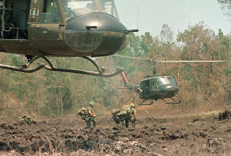 Description of  A helicopter hovers over the field, ready to load personnel and equipment during Operation Masher in the Vietnam War, May 7, 1966.  (AP Photo)