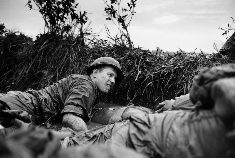 Description of  Pinned down by Viet Cong machine gun fire, a U.S. medic looks over at a seriuosly wounded comrade as they huddle behind a dike in a rice paddy, near Phu Loi, South Vietnam, August 14, 1966.  (AP Photo)
