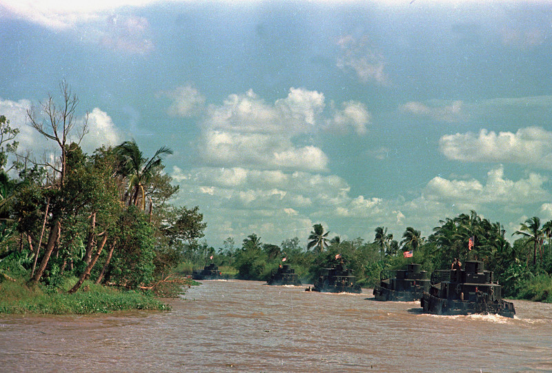 Description of  Riverine assault boats, Operation of the Riverine Force of the U.S. 9th Division, glide along the My Tho River, an arm of the Mekong Delta near Dong Tam, 35 miles southwest of Saigon, Vietnam, March 15, 1968.  (AP Photo)