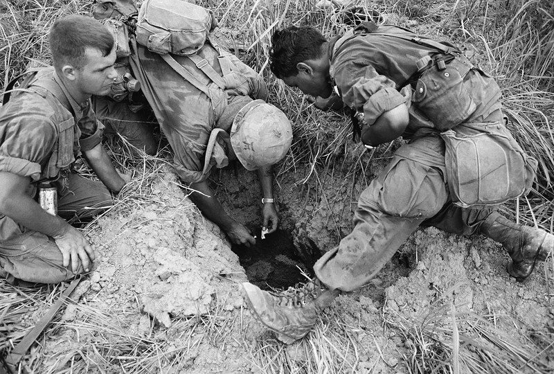 Description of  U.S. 25th Infantry division troops check the entrance to a Vietcong tunnel complex they discovered on a sweep northwest of their division headquarters at Cu Chi on Sept. 7, 1968 in Vietnam. (AP Photo)