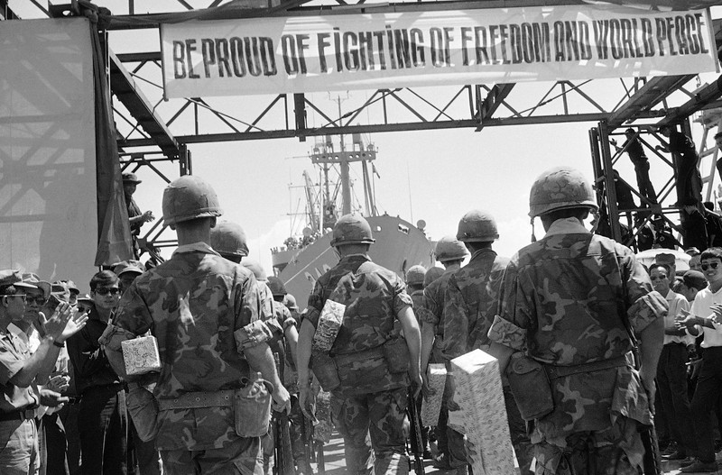 Description of  Banners of appreciation from the Vietnamese decorate the dock at Danang where a farewell ceremony was held by the Vietnamese Government for departing Marines of the 1st Battalion/9th Regiment, July 14, 1969. (AP Photo)
