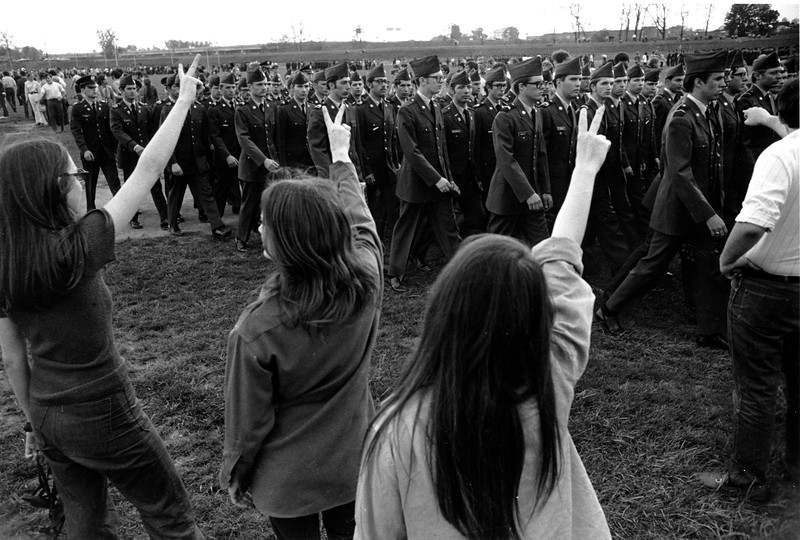 Description of  Demonstrators show their sign of protest as ROTC cadets parade at Ohio State University in May of 1970 during a ceremony in Columbus, Ohio during the Vietnam War. (AP Photo)