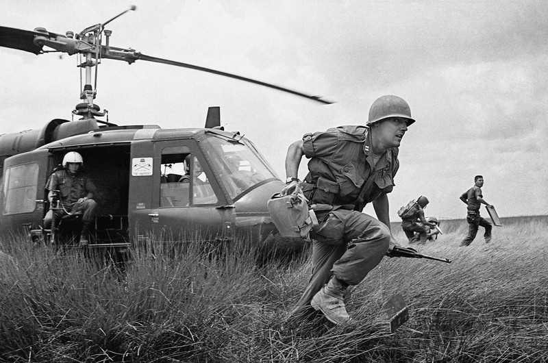 Description of  Capt. Donald R. Brown of Annapolis, Md., advisor to the 2nd Battalion of the 46th Vietnamese regiment, dashes from his helicopter to the cover of a rice paddy dike during an attack on Viet Cong in an area 15 miles west of Saigon on April 4, 1965 during the Vietnam War.  Brown's counterpart, Capt. Di, commander of the unit, rushes away in background with his radioman. The Vietnamese suffered 12 casualties before the field was taken. (AP Photo/Horst Faas)