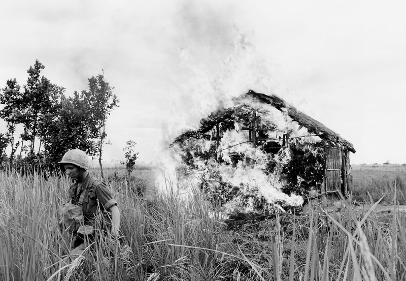 "Description of  A U.S. paratrooper moves away after setting fire to house on bank of the Vaico Oriental River, 20 miles west of Saigon on Jan. 4, 1966, during a ""scorched earth"" operation against the Viet Cong in South Viet Nam. The 1st battalion of the 173rd airborne brigade was moving through the area, described as notorious Viet Cong territory. (AP Photo/Peter Arnett)"