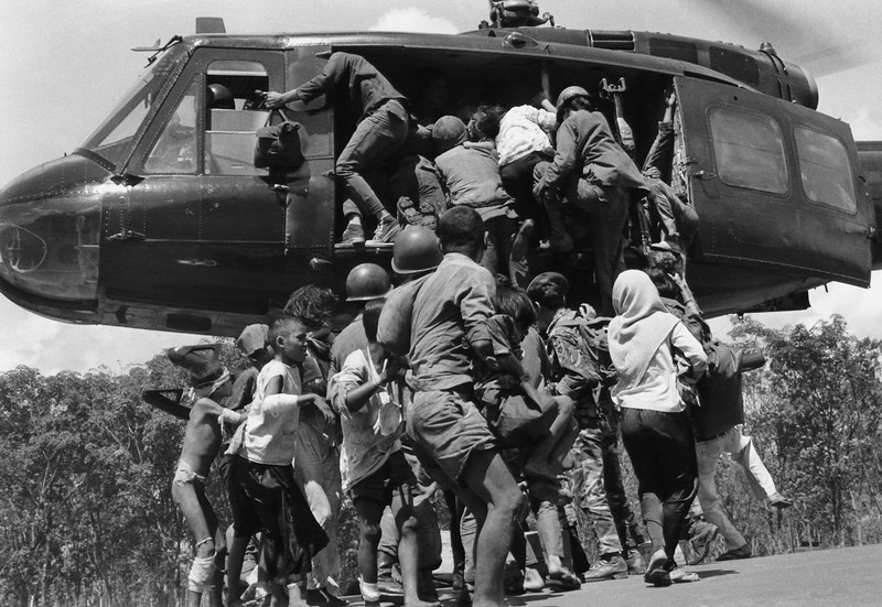 Description of  Lightly-wounded civilians and troops attempt to push their way aboard a South Vietnamese evacuation helicopter hovering over a stretch of Highway 13 near An Loc in Vietnam on June 25, 1972. (AP Photo)