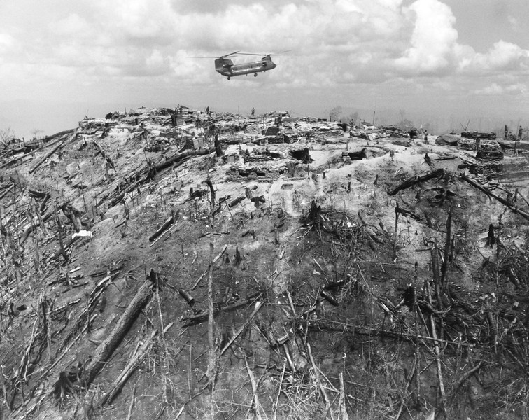 Description of  A supply helicopter comes in for a landing on a hilltop forming part of Fire Support Base 29, west of Dak To in South Vietnam's central highlands on June 3, 1968. Around the fire base are burnt out trees caused by heavy air strikes from fighting between North Vietnamese and American troops. (AP Photo)