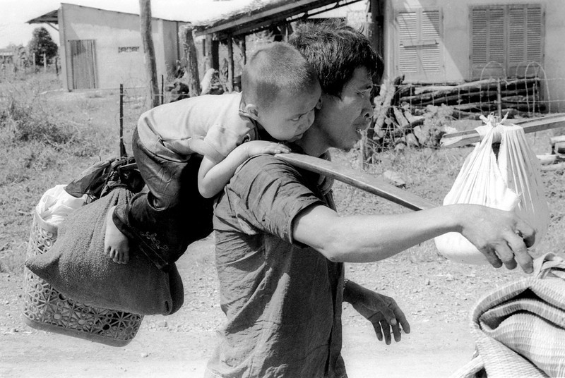 Description of  A South Vietnamese father carries his son and a bag of household possessions as he leaves his village near Trang Bom on Route 1 northwest of Saigon April 23, 1975. The area was becoming politically and militarily unstable as communist forces advanced, just days before the fall of Saigon.  (AP Photo/KY Mhan)