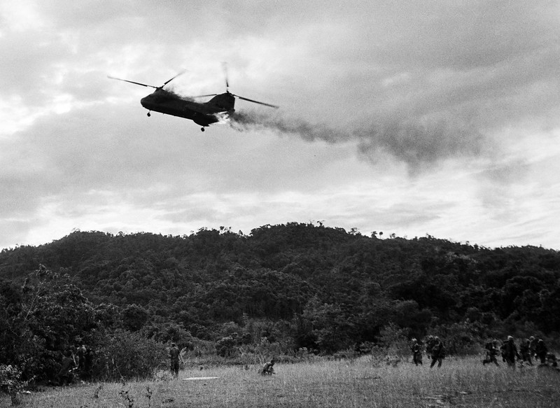 Description of  A U.S. Marine CH-46 Sea Knight helicopter comes down in flames after being hit by enemy ground fire during Operation Hastings, just south of the Demilitarized Zone between North and South Vietnam, July 15, 1966. The helicopter crashed and exploded on a hill, killing one crewman and 12 Marines. Three crewman escaped with serious burns. (AP Photo/Horst Faas)