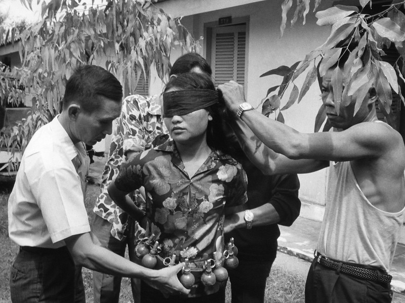Description of  Police in Da Nang cover the eyes of a woman who was an alleged member of a Viet Cong terrorist unit on Oct. 26, 1972. The woman was captured carrying 15 hand grenades, during the previous night's battle in Da Nang. (AP Photo)