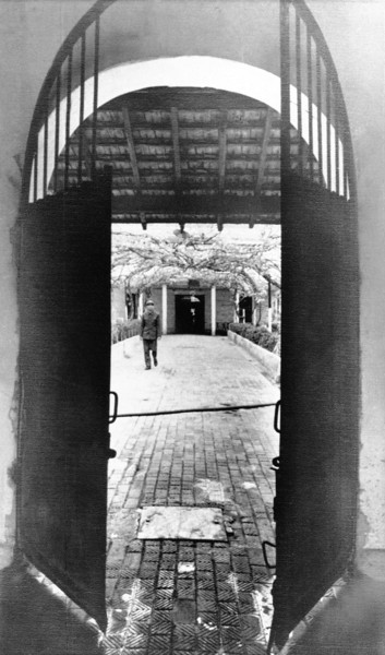 """Description of  An iron door opens on a compound of the """"Hanoi Hilton"""" prison, where the French once locked up political prisoners, shown March 18, 1973.  When 33 Americans were freed from it days earlier, all the cells were empty for the first time in more than eight years. Journalists were allowed to visit the prison, located in downtown Hanoi days after it was emptied. (AP Photo/Horst Fass)"""