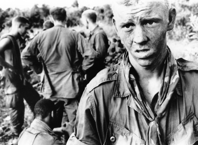 Description of  A young paratrooper with a mud-smeared face stares into the jungle in Vietnam on July 14, 1966, after fire fight with Viet Cong patrol in the morning. He is a member of C company, 2nd battalion, 173rd airborne brigade. (AP Photo/John Nance)