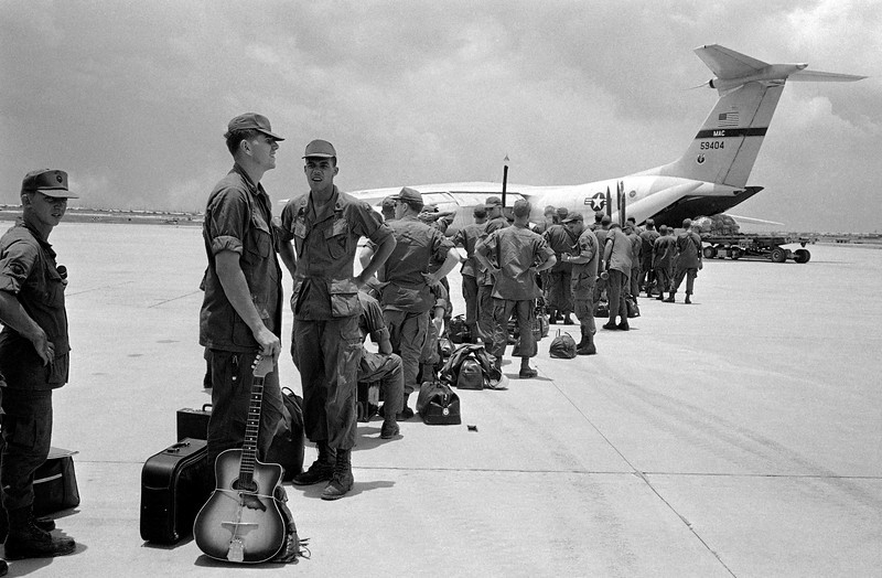 Description of  Some of the 300 troops of the 9th Infantry Division scheduled for departure from South Vietnam line up to board aircraft bound for Hawaii, August 27, 1969. (AP Photo)