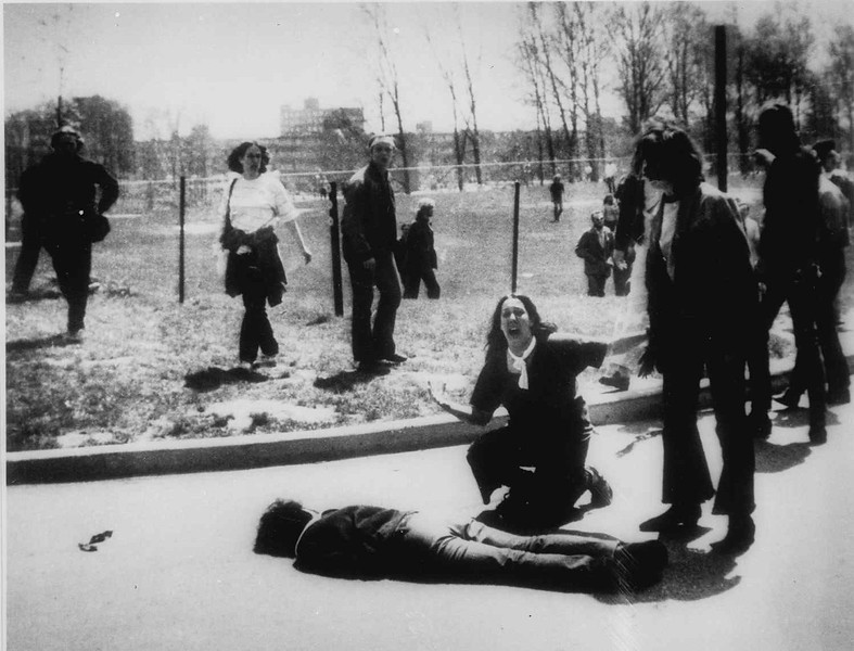 Description of  Mary Ann Vecchio gestures and screams as she kneels by the body of a student lying face down on the campus of Kent State University, Kent, Ohio on May 4, 1970. National Guardsmen had fired into a crowd of demonstrators, killing four. (AP Photo/John Filo)
