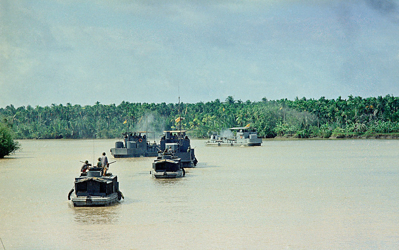 Description of  Vietnamese Navy boats laden with Vietnamese Army infantrymen swing along the Bien Tre river to launch a search mission some 50 miles south of Saigon in the Meking Delta's Kien Hoa province, July 11, 1967. Viet cong guerrillas fired on the flotlla from the brushy shoreline, but no major contact was made. (AP Photo)