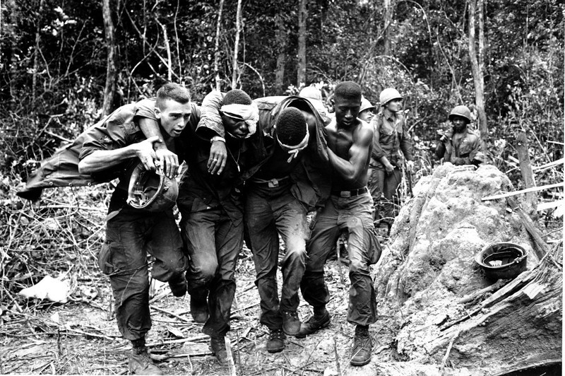 "Description of  Wounded U.S. paratroopers are helped by fellow soldiers to a medical evacuation helicopter on Oct. 5, 1965 during the Vietnam War. Paratroopers of the 173rd Airborne Brigade's First Battalion suffered many casualties in the clash with Viet Cong guerrillas in the jungle of South Vietnam's ""D"" Zone, 25 miles Northeast of Saigon. (AP Photo)"