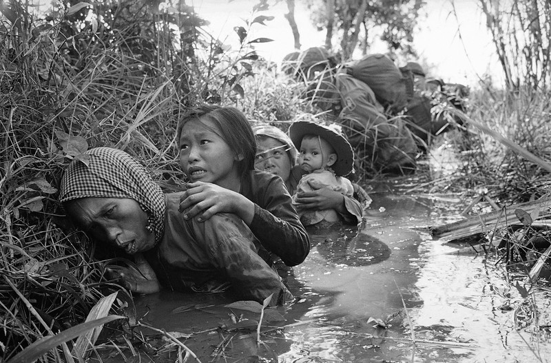 Description of  Women and children crouch in a muddy canal as they take cover from intense Viet Cong fire at Bao Trai in Jan. of 1966, about 20 miles west of Saigon, Vietnam. (AP Photo/Horst Faas, File)