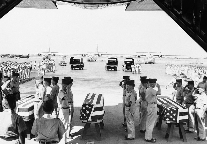 Description of  Caskets containing the bodies of seven American helicopter crewmen killed in a crash on January 11, 1963 were loaded aboard a plane on Monday, Jan. 14 for shipment home. The crewmen were on board a H21 helicopter that crashed near a hut on an Island in the middle of one of the branches of the Mekong River, about 55 miles Southwest of Saigon. (AP Photo)