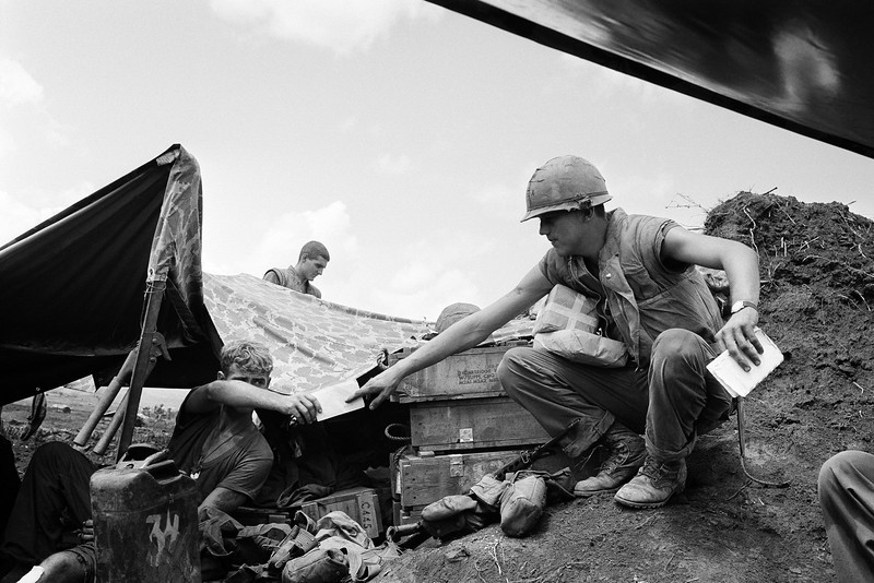 Description of  The address is muddy bunker and the mailman wears a flak vest as CPL. Jesse D. Hittson of Levelland, Texas, reaches out for his mail at the U.S. Marine Con Thien outpost two miles south of the demilitarized zone in South Vietnam on Oct. 4, 1967. (AP Photo/Kim Ki Sam)